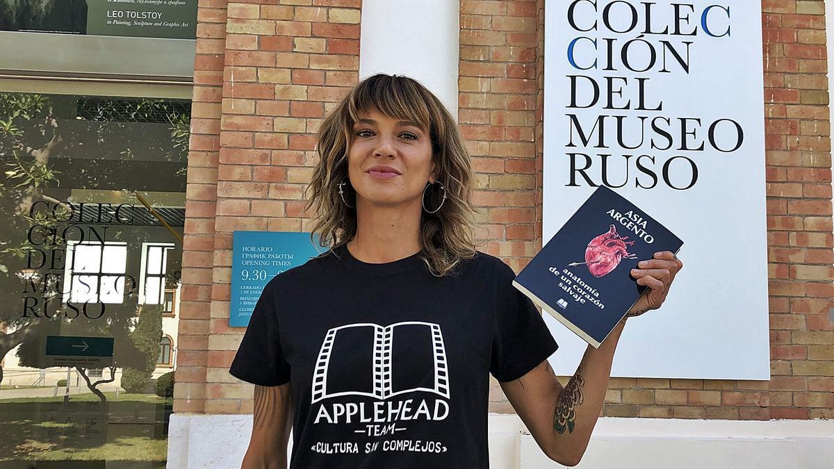 Asia Argento, posando con su libro y con una camiseta de la editorial malagueña, en la entrada del Museo Ruso de Málaga.