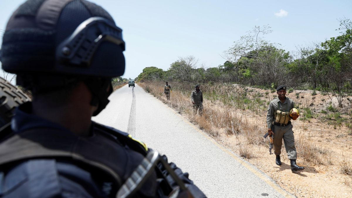 Rwandan police officer watches Mozambique police patrol near the town of Oasse