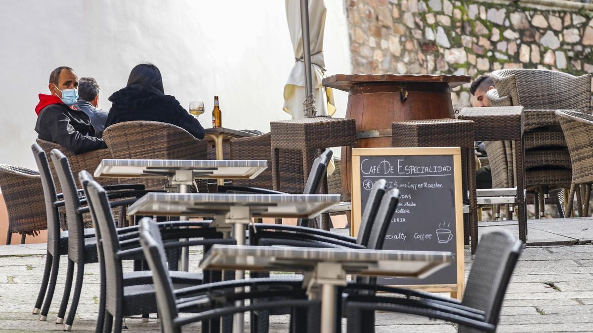 Varias personas protegidas con mascarillas, sentadas en una terraza de un establecimiento del centro de Cáceres.