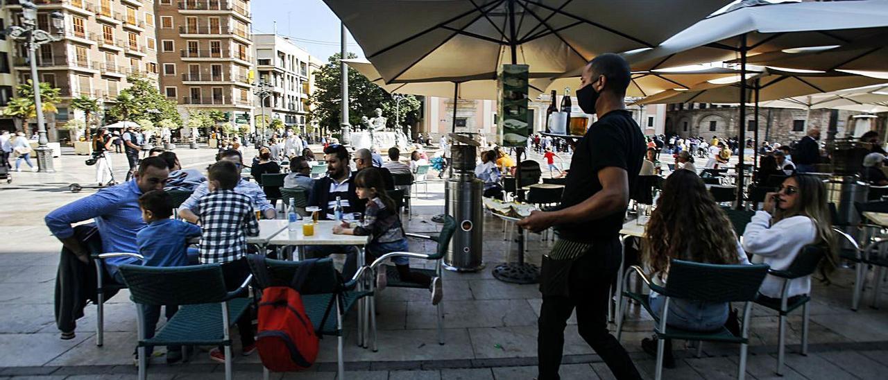 Un empleado atiende en una terraza de la plaza de la Virgen de València, el domingo.   EDUARDO RIPOLL