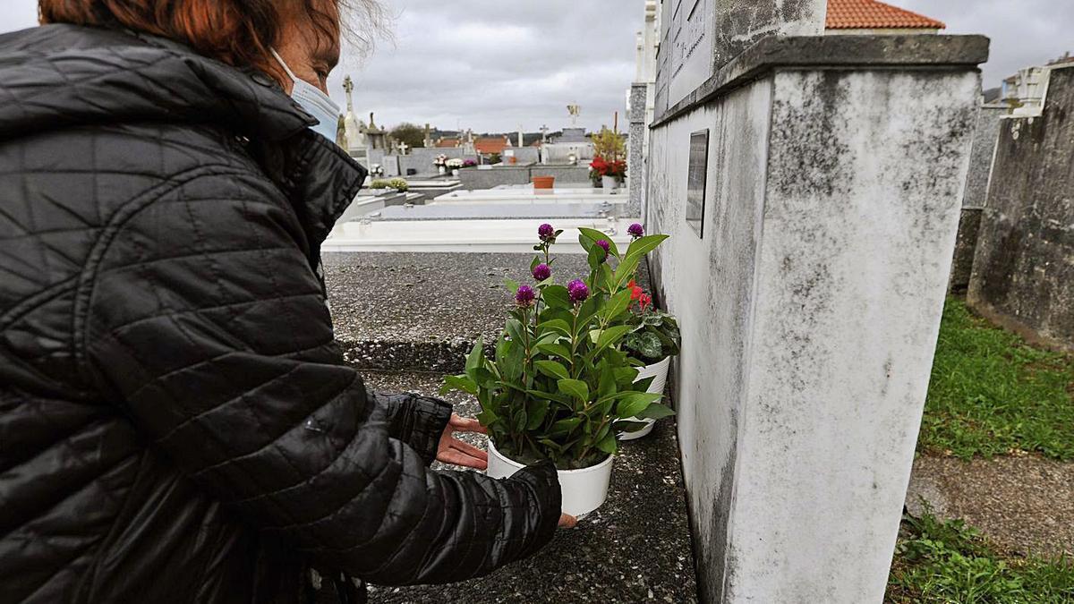 Una mujer, ayer, colocando flores en una tumba del cementerio viejo de Lalín.    // BERNABÉ/JAVIER LALÍN