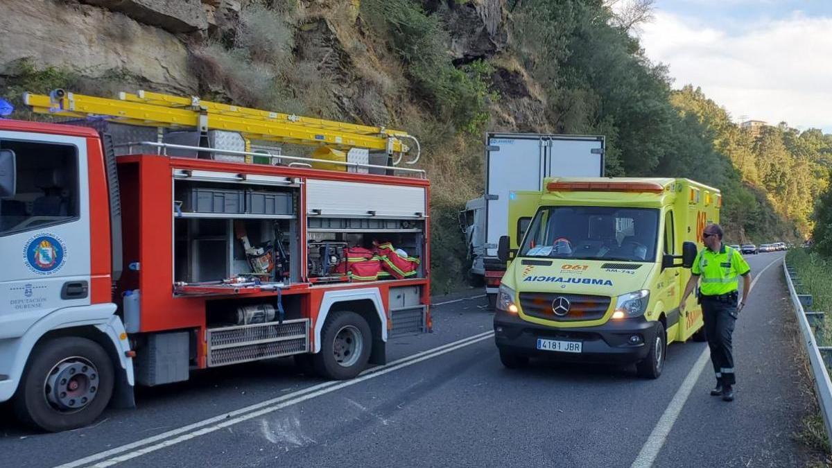 Los servicios de emergencias con el camión accidentado al fondo. // FdV