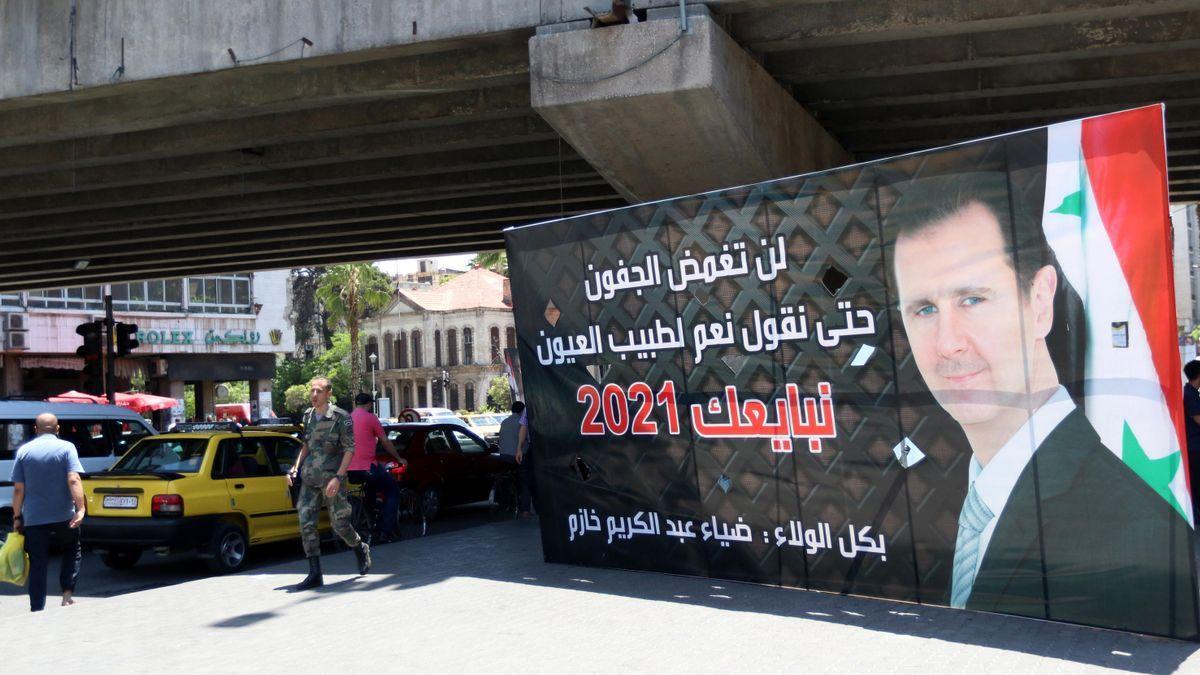 Varios peatones pasa junto a un cartel electoral que muestra al presidente sirio, Bachar Al Assad.