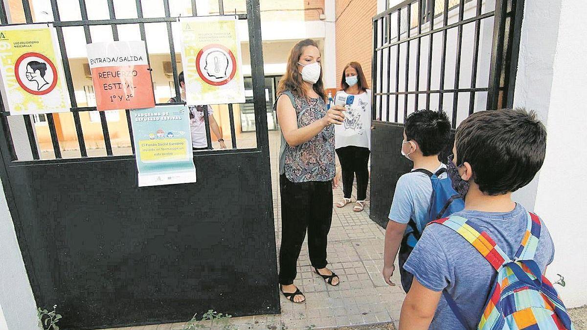 Una mujer toma la temperatura a un niño a su entrada al colegio.