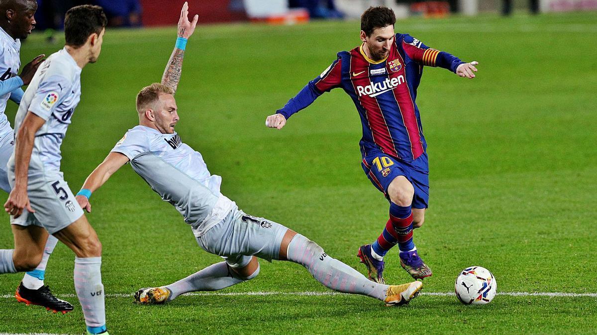 Uros Racic se estira para intentar cortar el avance de Messi en la visita del Valencia CF al Camp Nou.  | EFE'