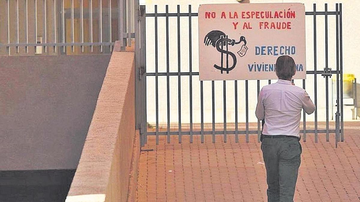Un hombre observa un cartel de protesta de los vecinos, el año pasado, en el acceso al bloque de viviendas.