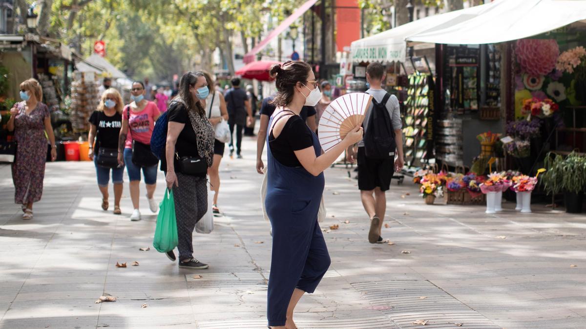 Gente pasea por la Rambla de Barcelona.