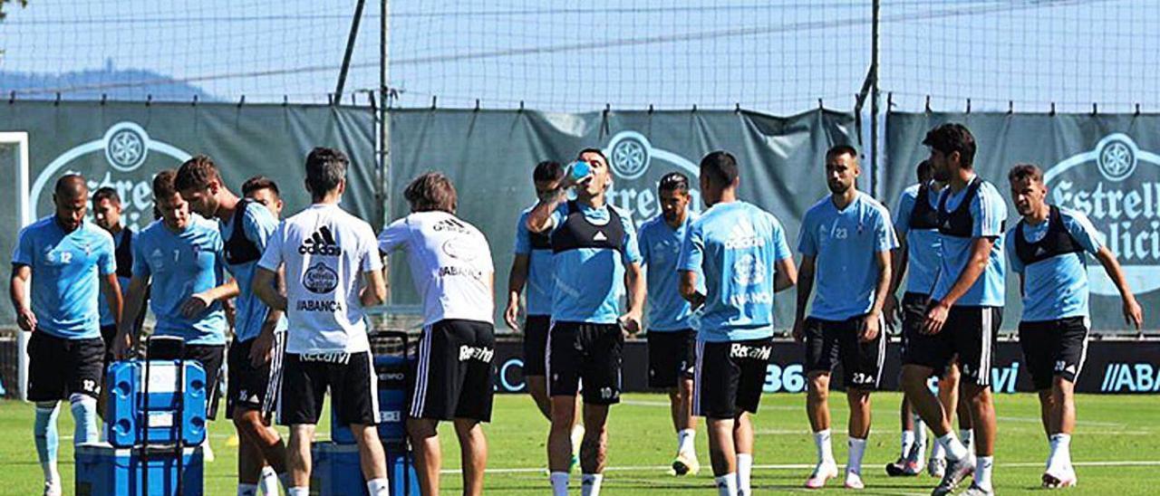 Los jugadores del Celta se toman un receso para refrescarse durante el entrenamiento matinal celebrado ayer en A Madroa.