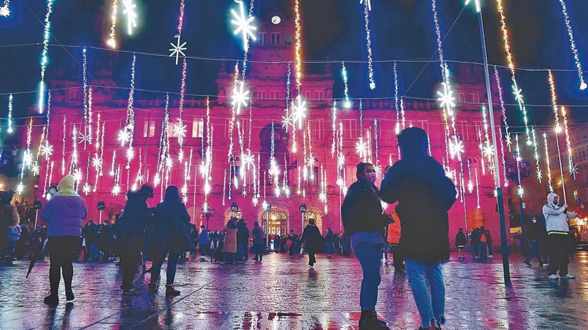 Coruñeses observan el alumbrado navideño, en María Pita, el pasado mes de diciembre.     // C. PARDELLAS