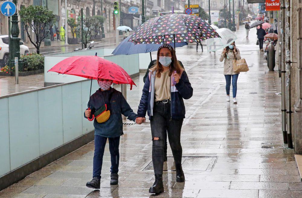 Los viandantes en el centro de Vigo se pertrecharon con paraguas