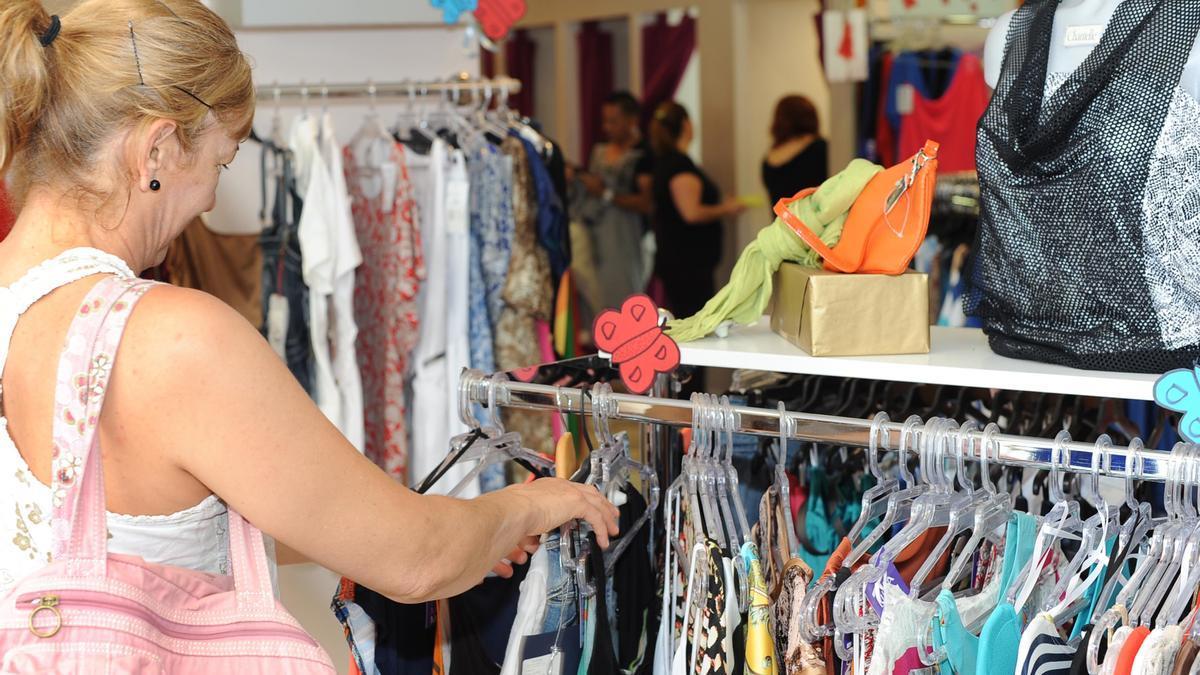 Una mujer mira ropa en un pequeño comercio en una imagen de archivo.