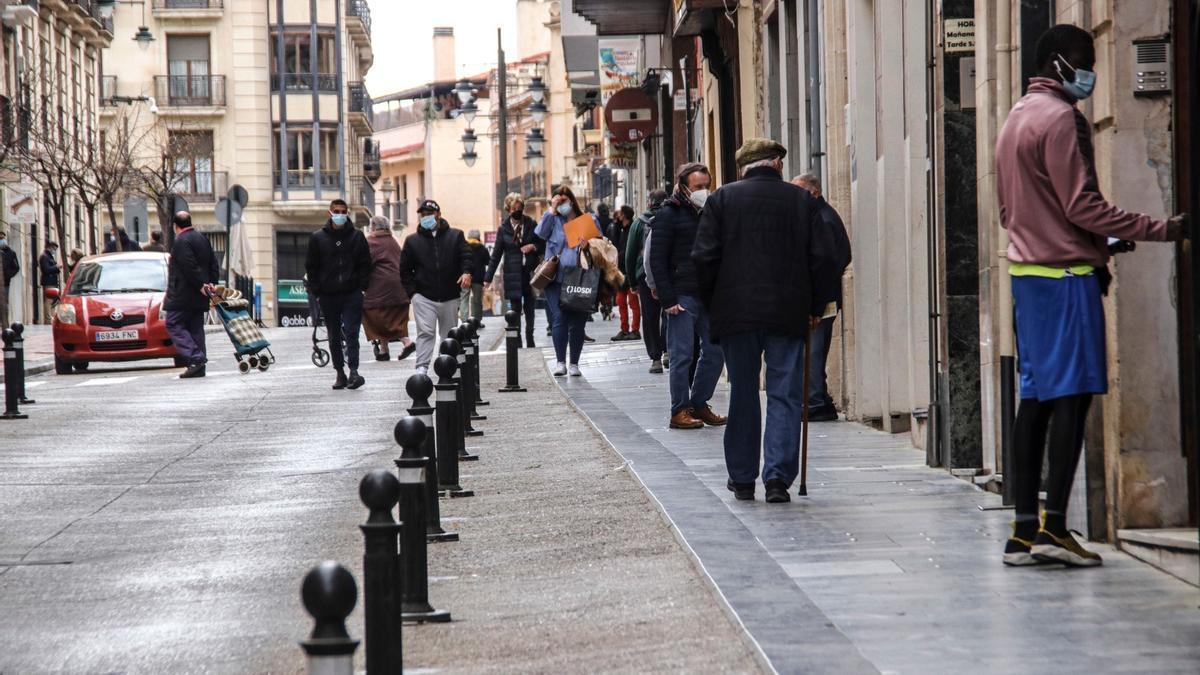 Pedestrians walk through one of the pedestrianized streets of the Alcoy urban area.