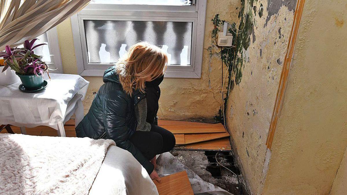 Carmen Pardo, en un lugar de su casa dañado por la humedad causada por el edificio anexo.