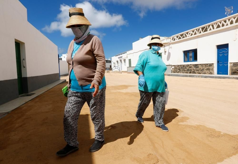 Two women walk down a street, as the country ...