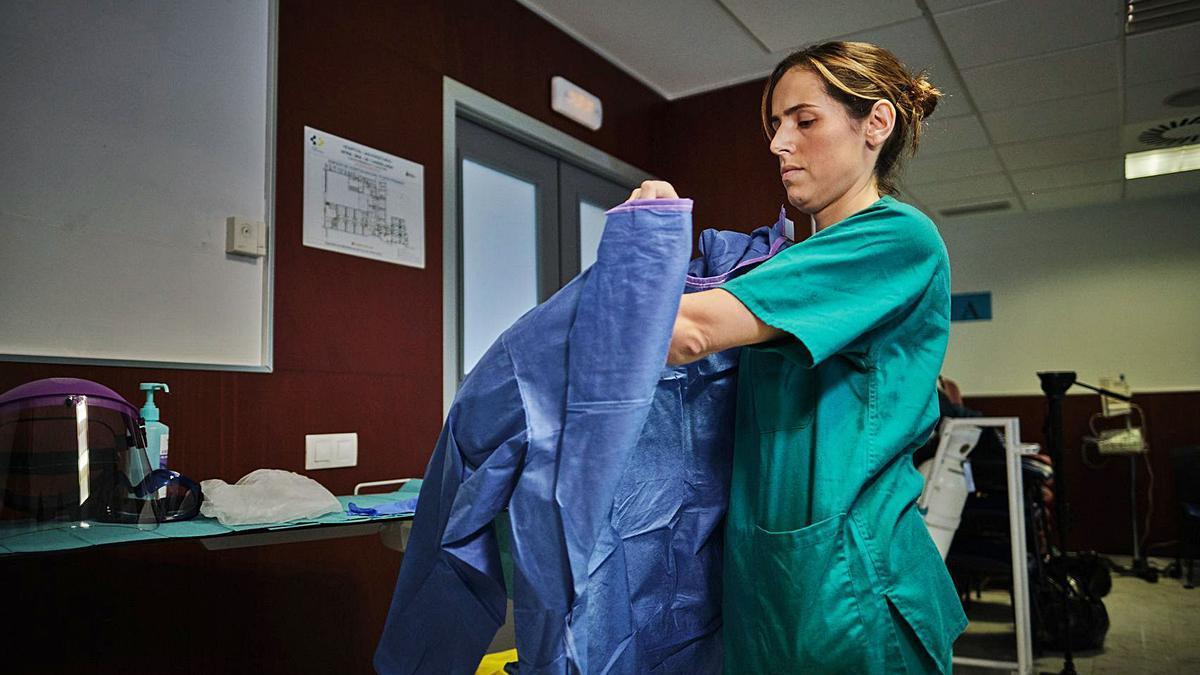 Una sanitaria se prepara para atender a un paciente con coronavirus.