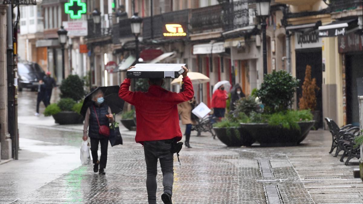 Varias personas pasean por la calle bajo la lluvia.