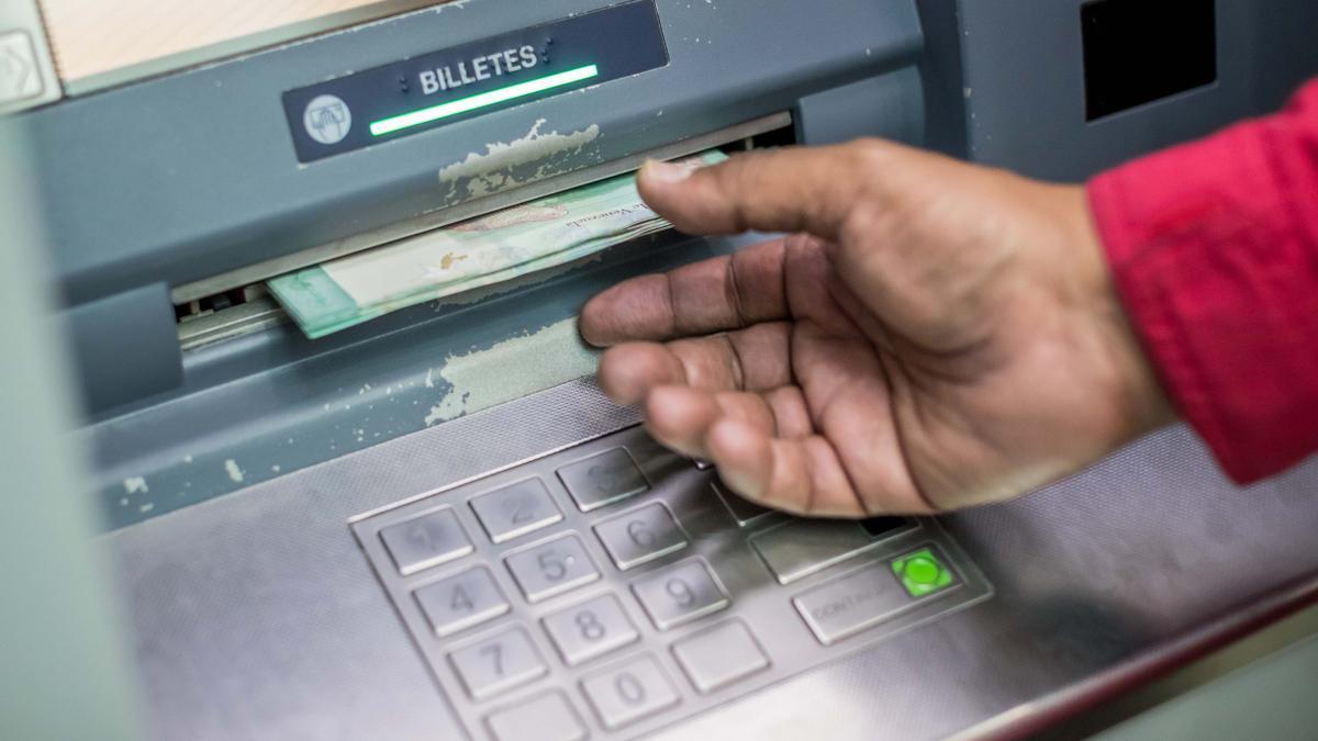 Un hombre saca dinero en un cajero automático.