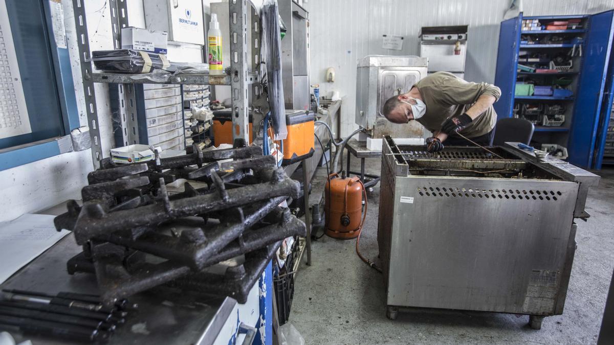 Un operario de Exposervi reacondiciona  maquinaria vendida por negocios  hosteleros que han cerrado.