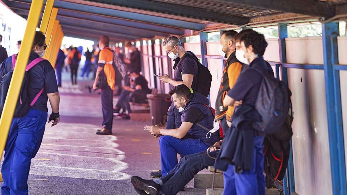 Trabajadores de Ford esperan al autobús al término de su jornada, el pasado marzo. | PERALES IBORRA