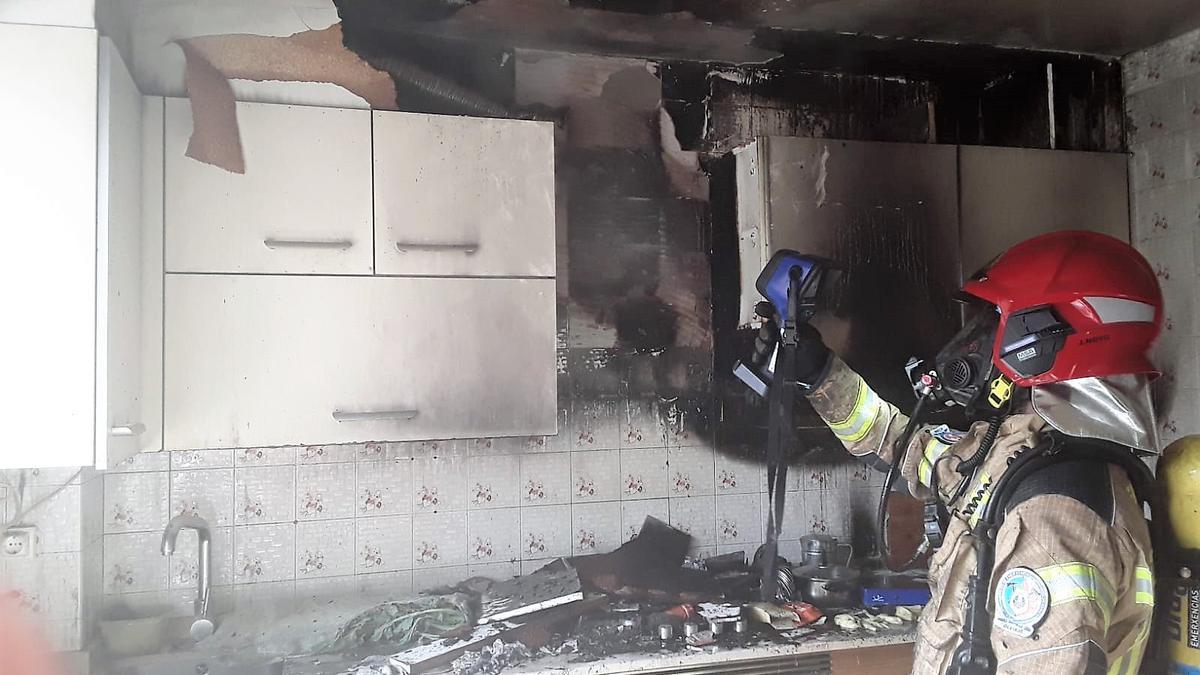 Efectivo de emergencias mide la temperatura en la cocina tras el incendio