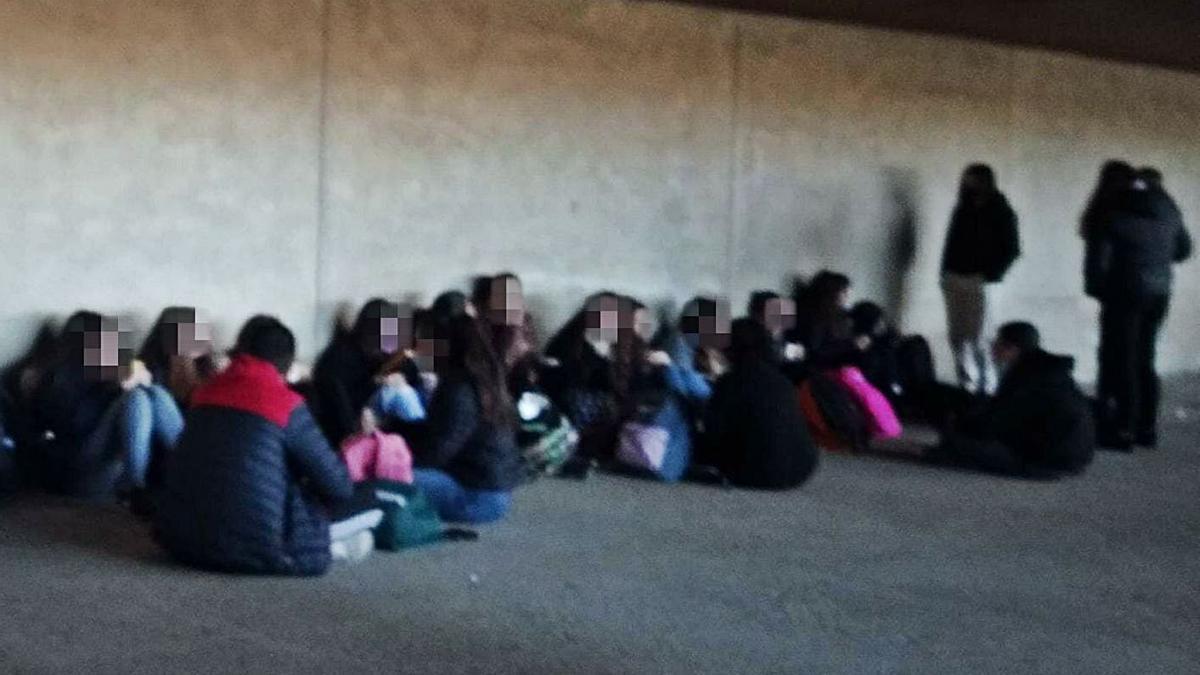 Imagen, captada en el patio, de los alumnos sentados sin guardar la distancia y sin mascarilla.