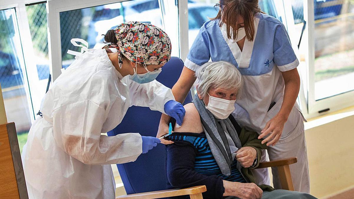 Dos sanitarias administran a una residente la primera dosis de la vacuna en una residencia.  | LEVANTE-EMV