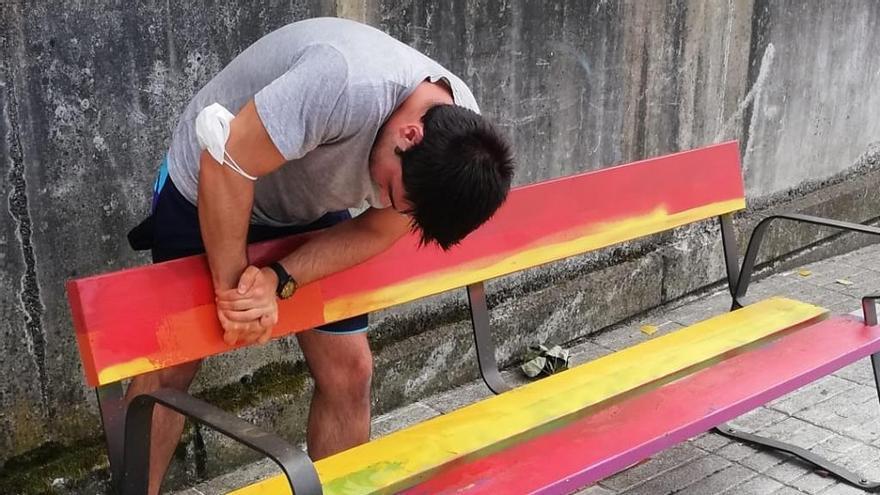 Iago Casal, ayer, retirando la pintura de spray con la unos vándalos taparon los colores arcoíris del banco de Sada