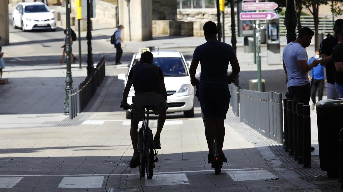 Un ciclista y un usuario de patinete eléctrico.