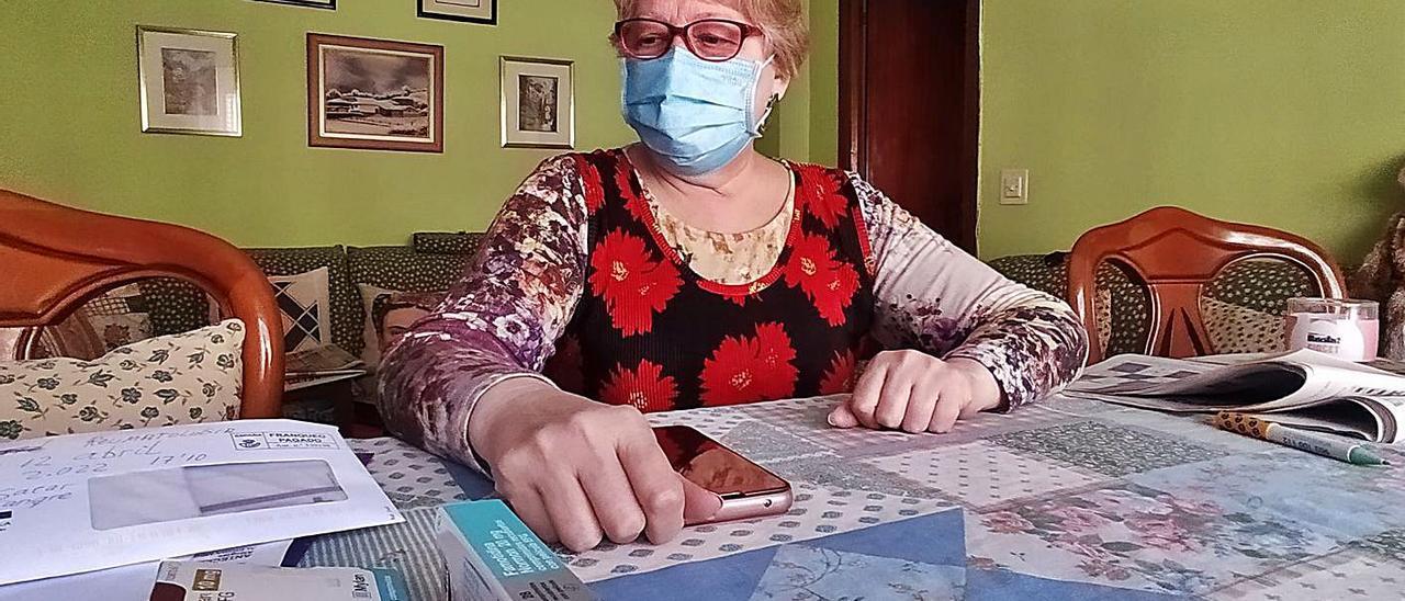 María Elena Hernando, ayer, en su casa, con varios informes médicos y medicamentos sobre la mesa. | D. M.