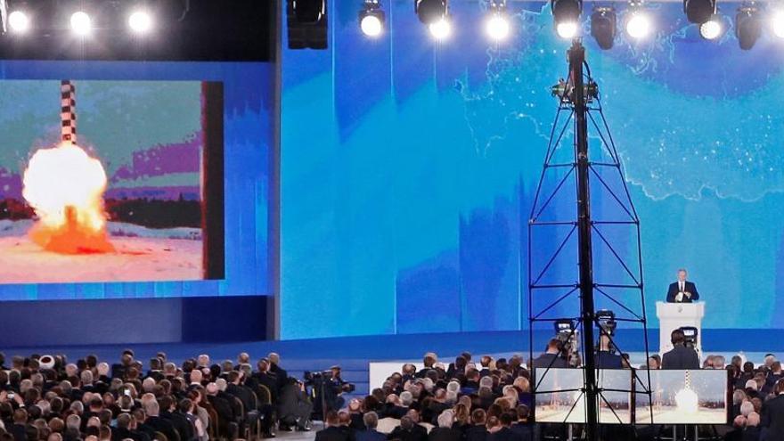 Putin da un discurso ante la Asamblea Federal mientras la pantalla muestra los nuevos misiles.