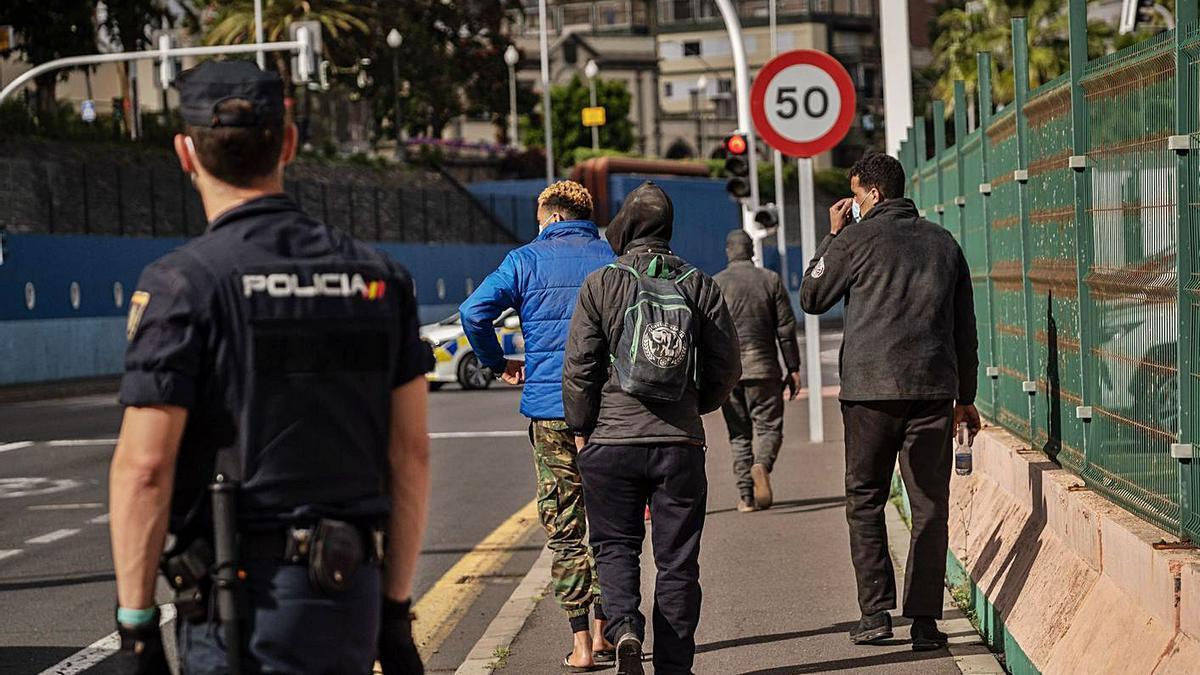 Varios migrantes son conducidos por la Policía hasta el exterior del Puerto de Santa Cruz de Tenerife. | | ANDRÉS GUTIÉRREZ