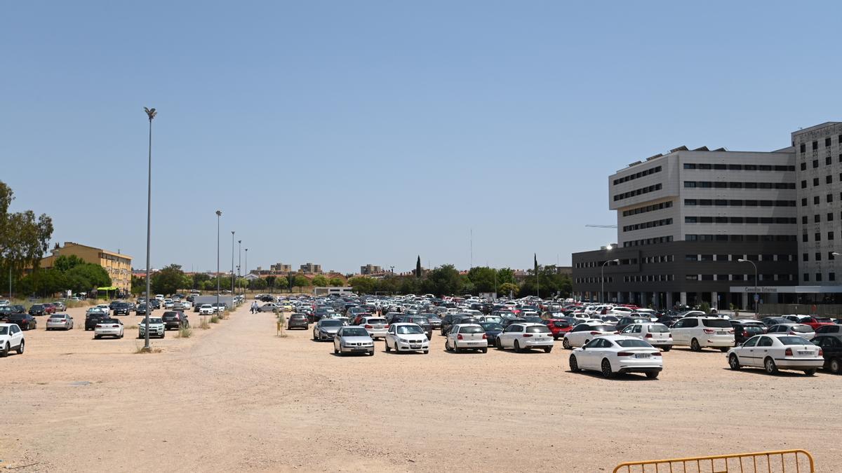Vehículos estacionados junto al hospital Universitario en la parte sin asfaltar.