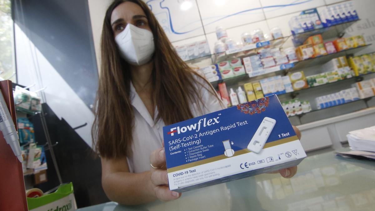Una empleada de farmacia con un test de autodiagnóstico del covid-19.