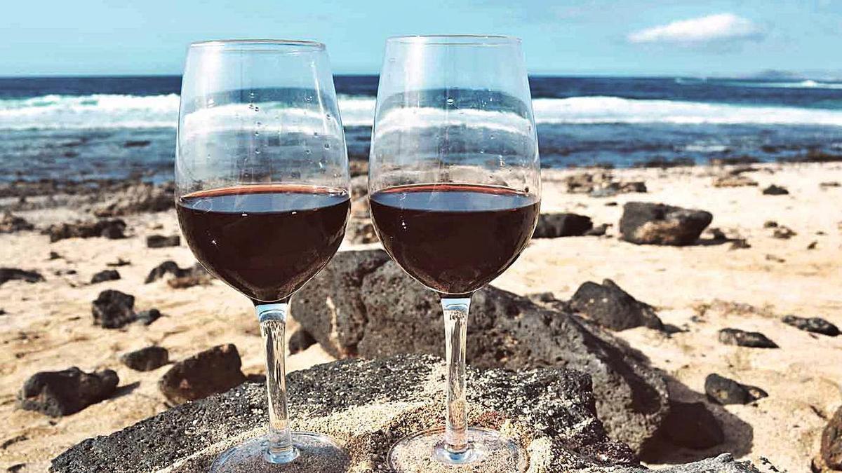 Copas de vino elaborado en Canarias en una playa de las islas.