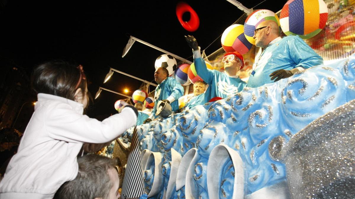 Sardineros de Momo reparten juguetes desde la carroza.