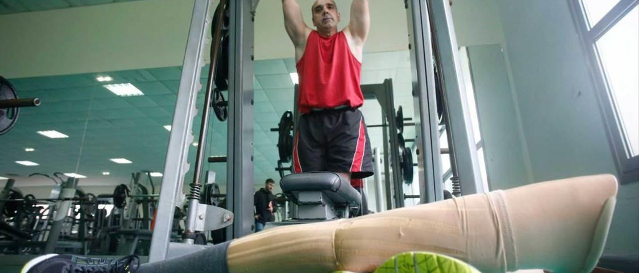 Paco Galán entrena dominadas; en primer término, las prótesis que usa para caminar.