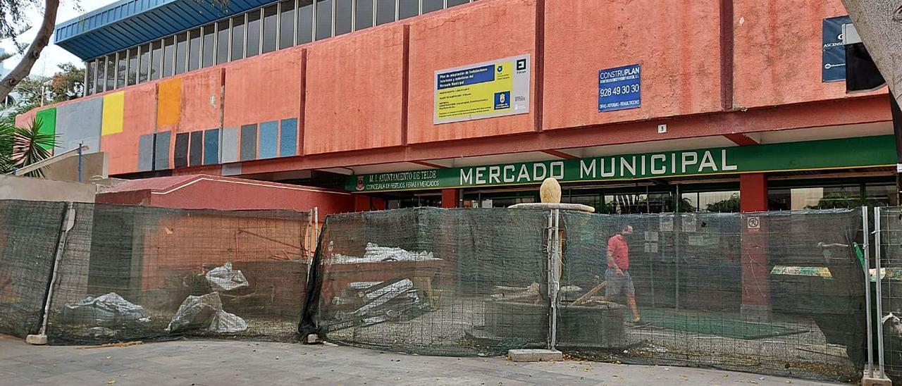 Fachada del mercado municipal con una valla para delimitar las obras que se efectúan en el interior y entorno.