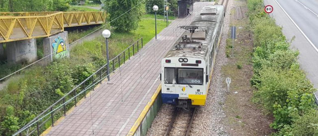 Un tren de la línea Gijón-Laviana, en el apeadero de Carrocera. En el círculo, una pintada en una de las estaciones del Nalón. | L. M. D.