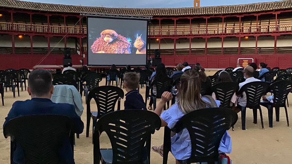 Varias personas disfrutan en un cine de verano al aire libre