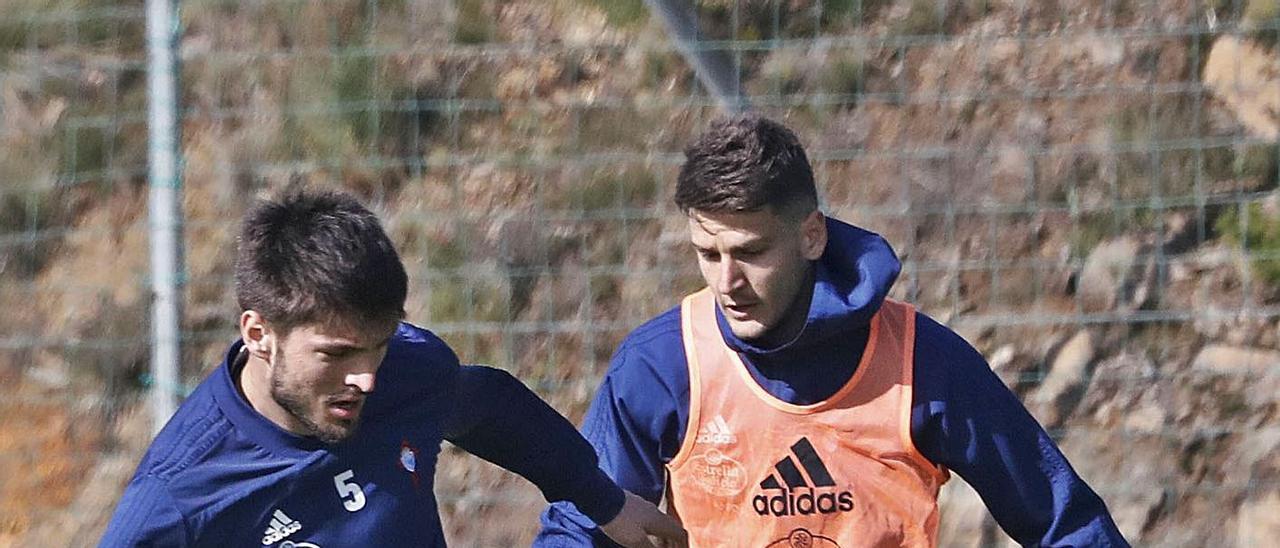 Okay y Radoja disputan el balón durante un entrenamiento en abril de 2019 en A Madroa . |  // JOSÉ LORES
