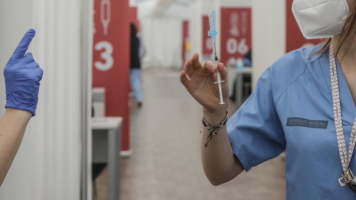 Archivo - Una profesional sanitaria sostiene una jeringuilla con la vacuna de AstraZeneca