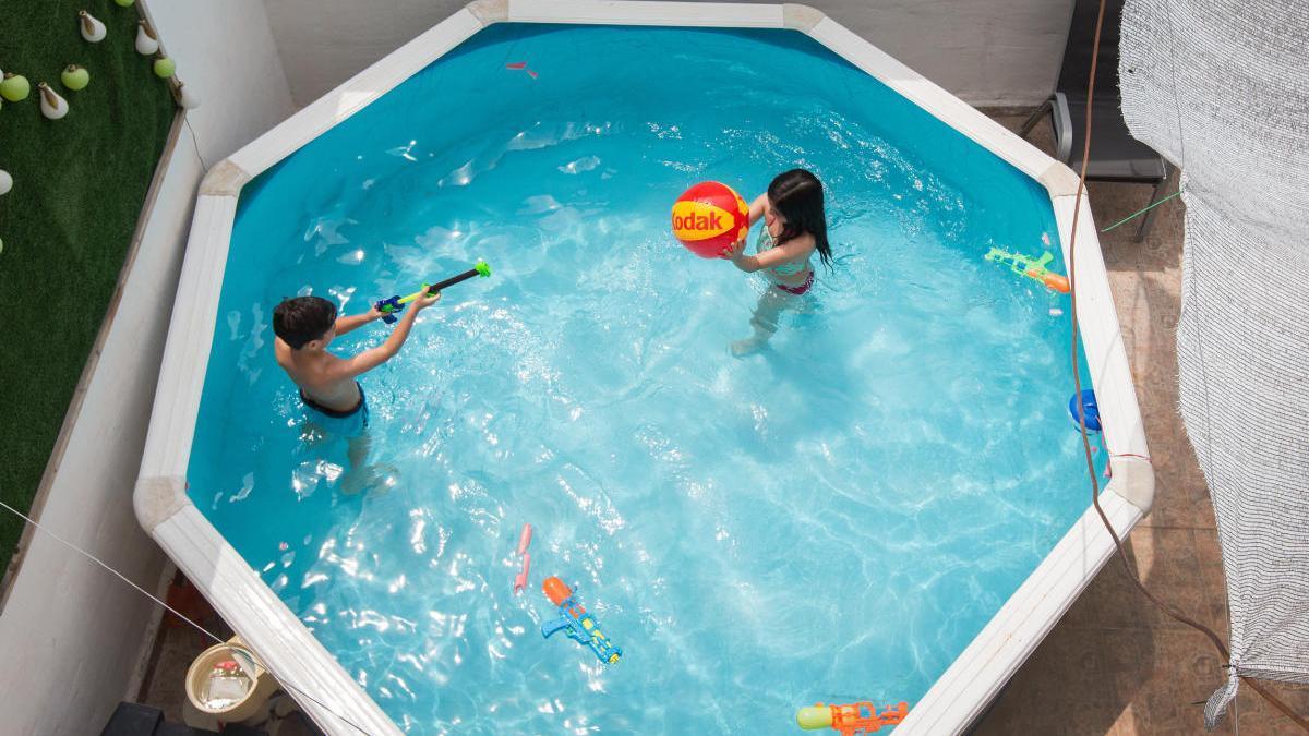 Dos niños juegan en una piscina portátil.