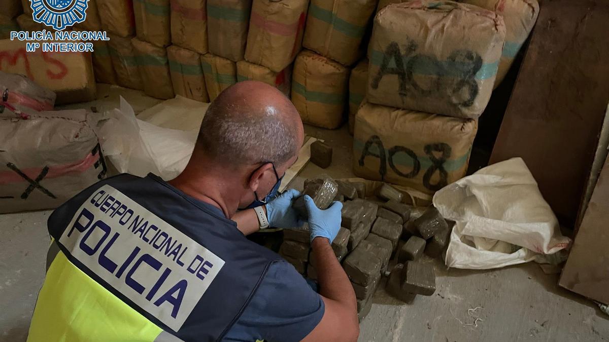 Un agente de la Policía comprueba el contenido de los fardos hallados en una nave de Dos Hermanas