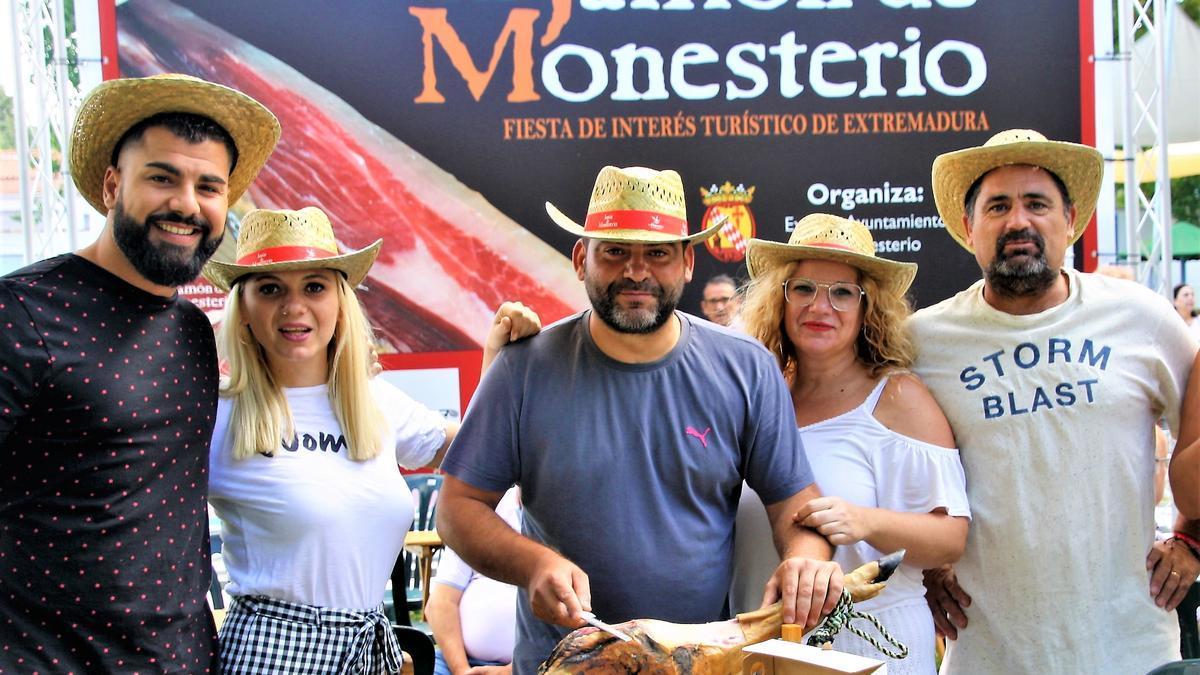 Participantes en la Fiesta del Jamón con el logo oficial al fondo