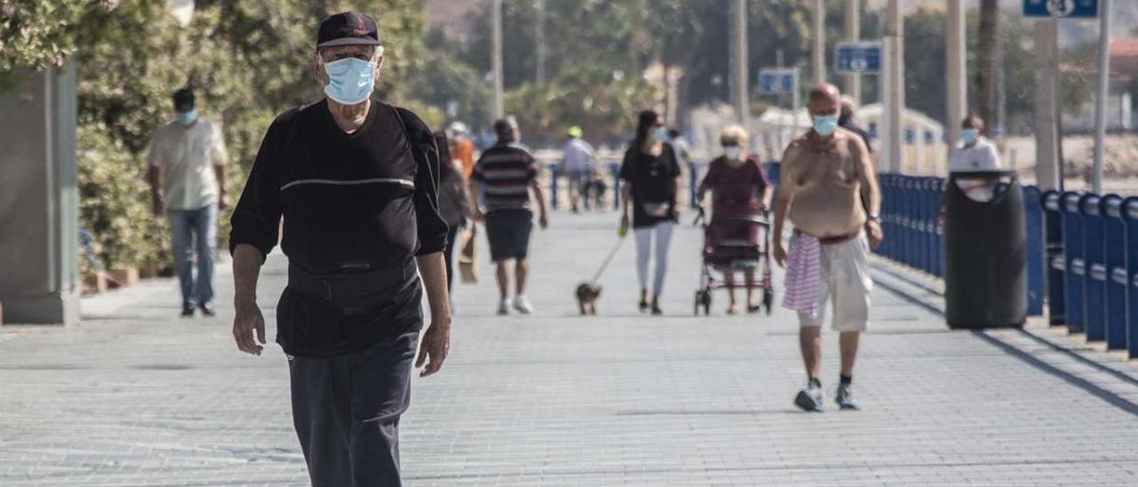 Gente con mascarilla paseando por el Postiguet.