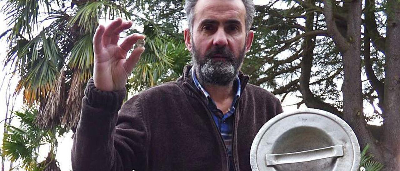 Lucas Santiago, tras antiguos bidones de leche, muestra en su mano la réplica en joya de la tapa. | D. Á.