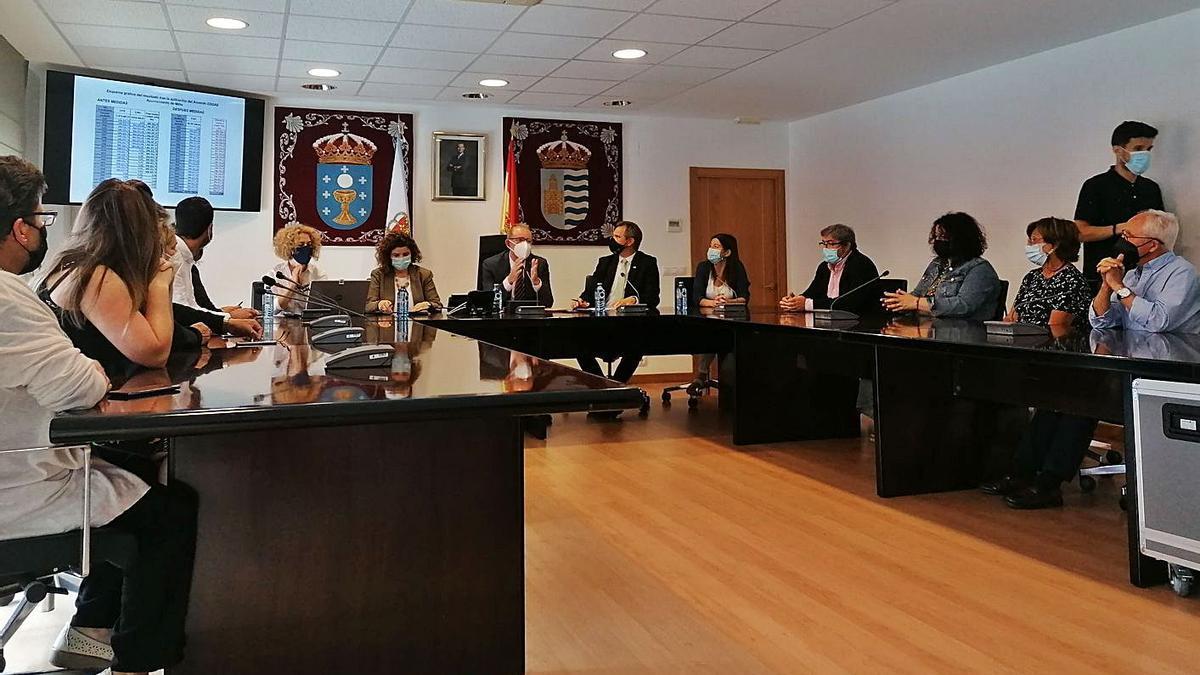 El delegado del Gobierno, el alcalde y la Corporación de Miño, ayer durante el anuncio de la moratoria.     // LOC