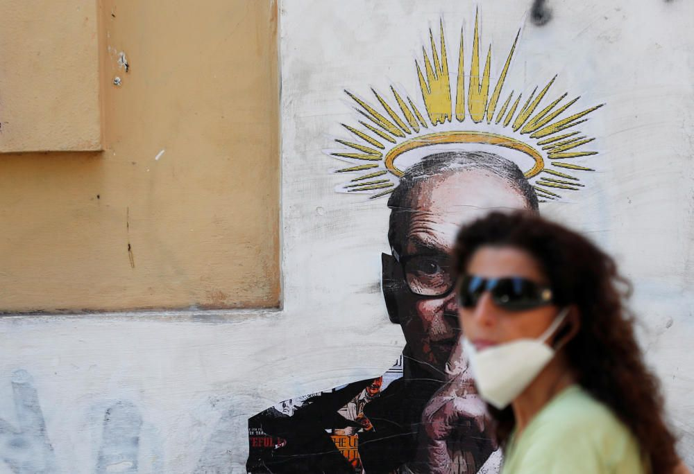 A woman walks past a mural dedicated to Italian ...