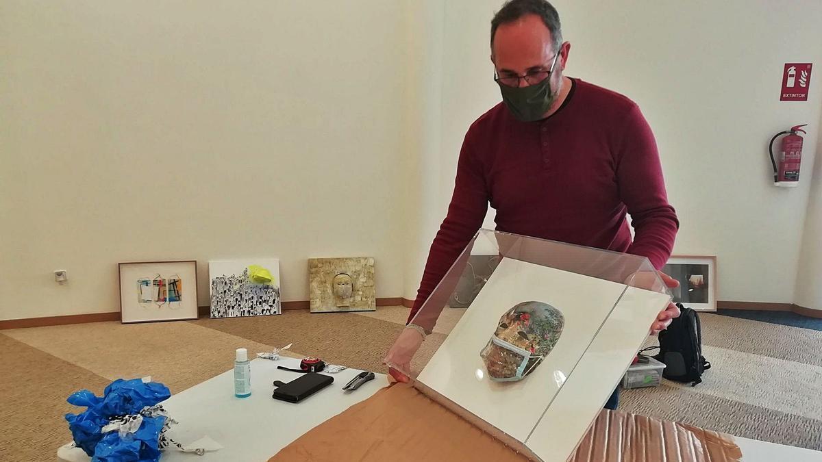 Hipólito Guillén, técnico de montaje, desembala la obra de Vicente Alonso.