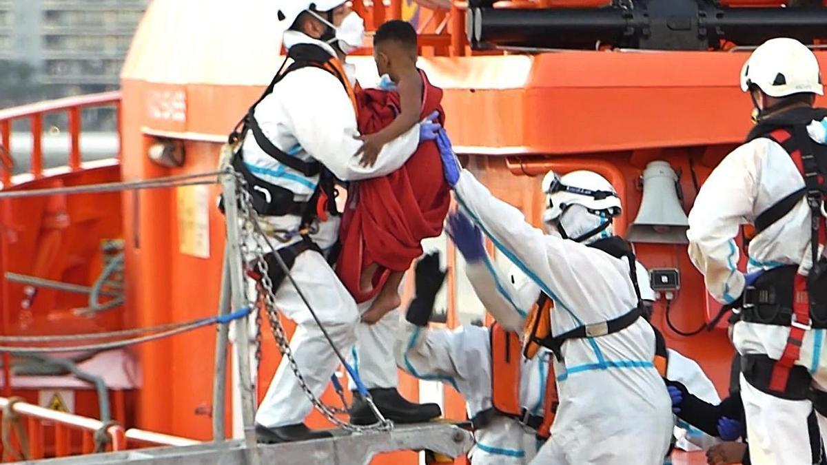 Miembros de Salvamento Marítimo  ayudan a un menor a bajar de la guardamar en Arguineguín.